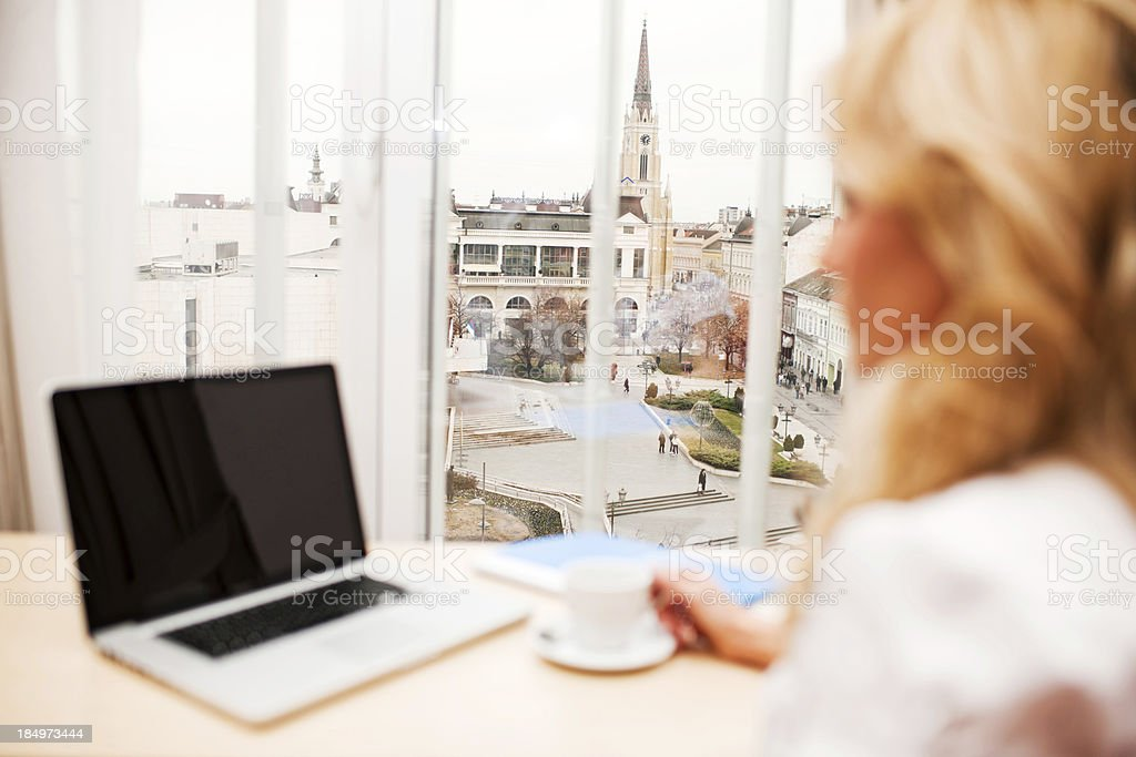 Businesswoman using laptop and drinking coffee. royalty-free stock photo