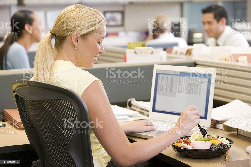 Mujer de negocios con ordenador portátil y comiendo ensalada - Foto de stock de Comer libre de derechos
