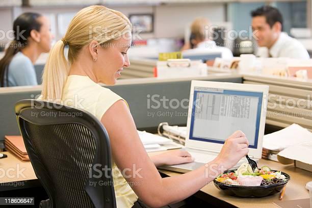Mujer De Negocios Con Ordenador Portátil Y Comiendo Ensalada Foto de stock y más banco de imágenes de Comer
