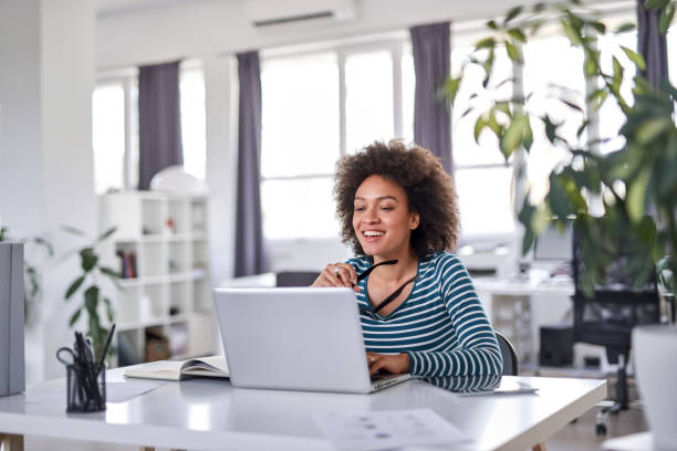 Businesswoman using laptop and holding eyeglasses in hand while sitting in office. Smiling mixed race businesswoman holding eyeglasses and looking at laptop while sitting in modern office. design occupation stock pictures, royalty-free photos & images
