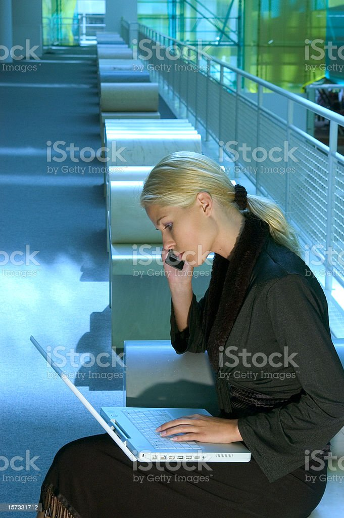 businesswoman using laptop and mobile phone royalty-free stock photo
