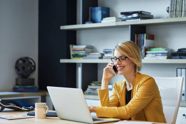 zakenvrouw met laptop en smartphone bij bureau - business woman phone stockfoto's en -beelden
