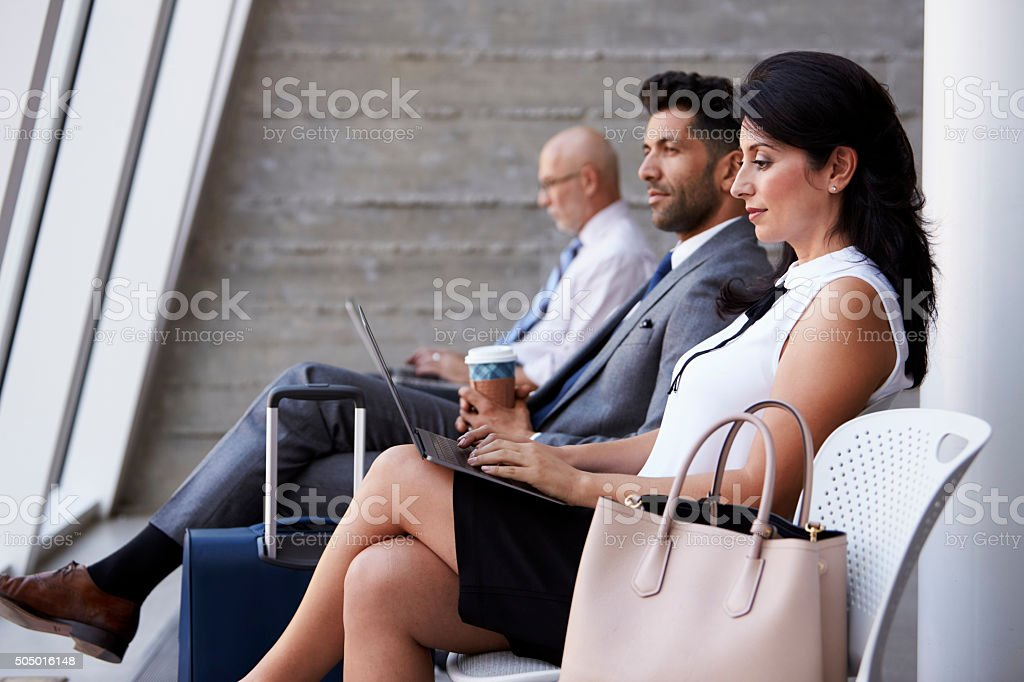 Businesswoman Using Laptop In Airport Departure Lounge stock photo