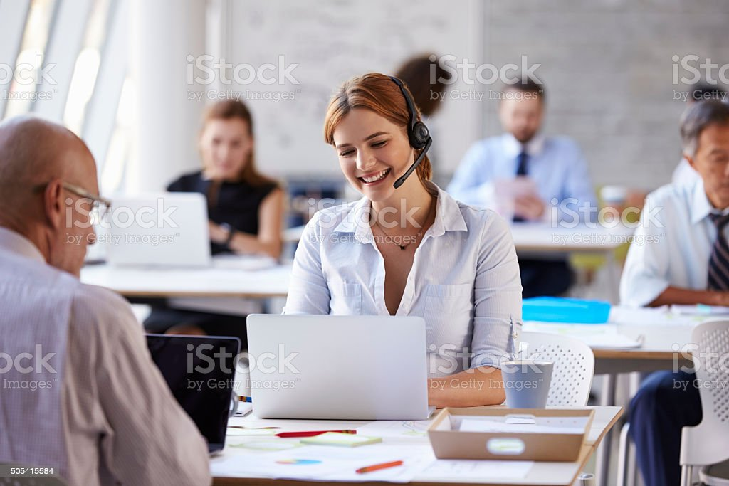 Businesswoman Using Laptop In Customer Service Department stock photo