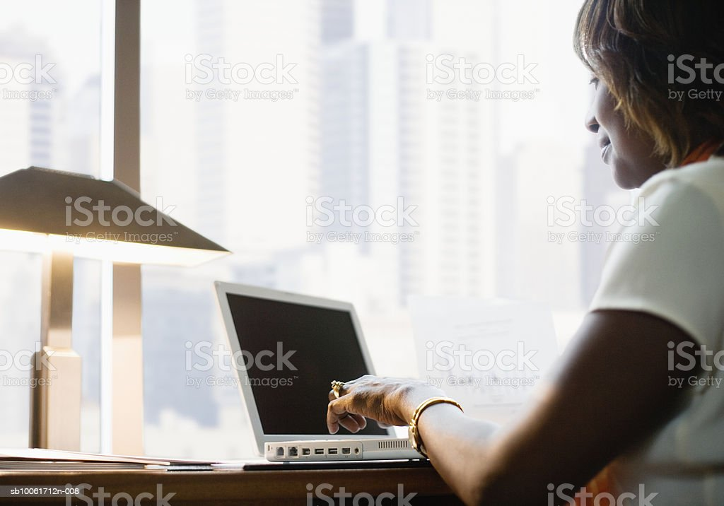 Businesswoman using laptop in hotel room foto de stock libre de derechos
