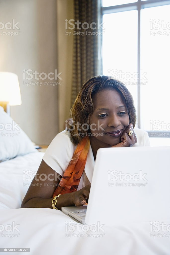 Businesswoman using laptop in hotel room, smiling 免版稅 stock photo