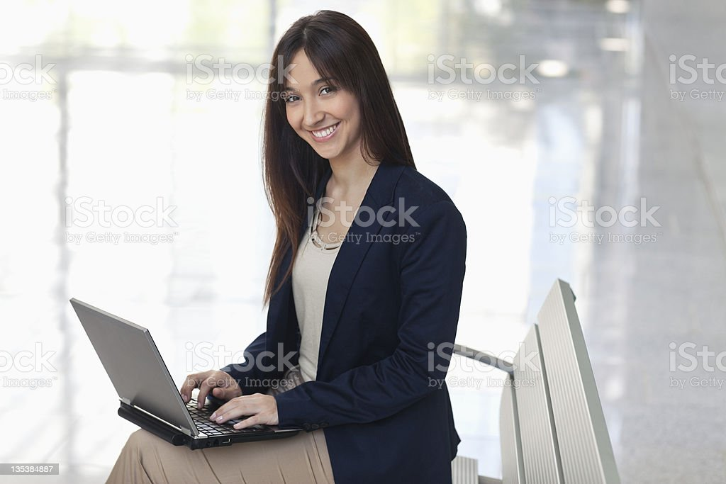 Businesswoman using laptop in lobby royalty-free stock photo