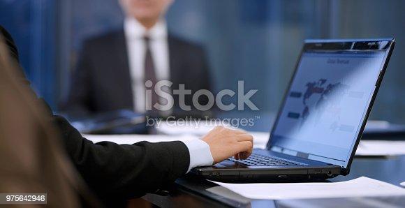 istock Businesswoman using laptop in meeting 975642946