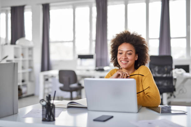 Businesswoman using laptop in office. Beautiful smiling mixed race businesswoman dressed casual sitting in office and using laptop. using computer stock pictures, royalty-free photos & images