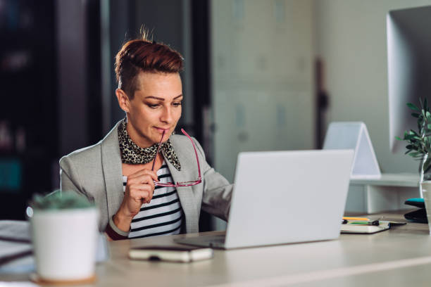 Businesswoman using laptop in the office and smiling stock photo