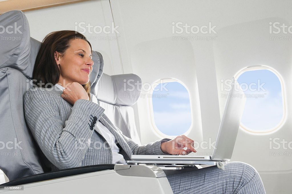 Businesswoman using laptop on airplane stock photo