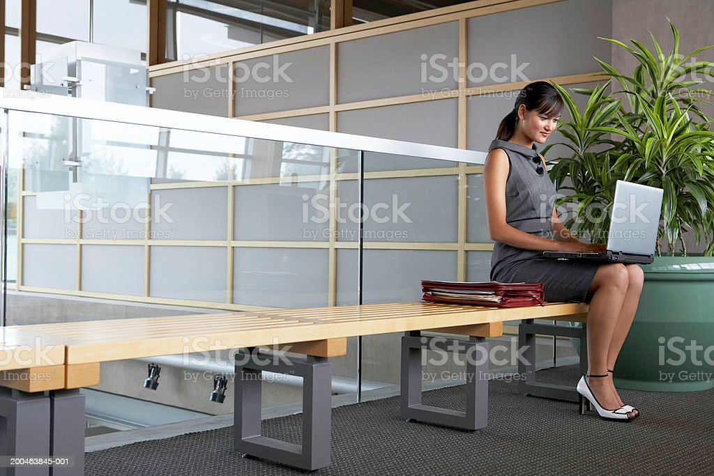 Businesswoman using laptop on bench in lobby royalty-free stock photo