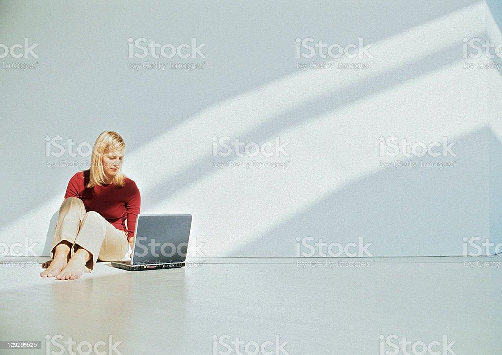 Деловая женщина с помощью ноутбука на этаже стоковое фото