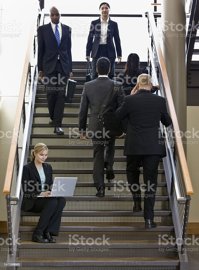 Businesswoman Using Laptop on Stairs stock photo