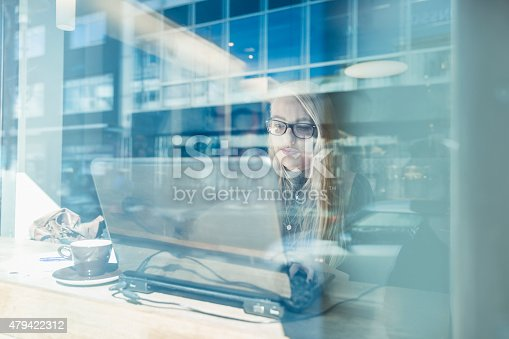 A photo of businesswoman using laptop seen through glass window. Professional is with computer at table in cafe. Young female is working in coffee shop.