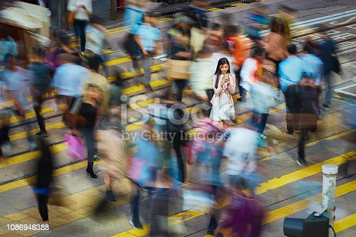 High angle view of young professional using mobile phone amidst crowd. Businesswoman is standing on busy street. She is surrounded by people in city.