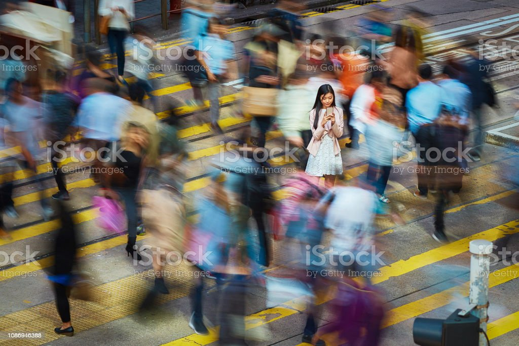 Businesswoman using mobile phone amidst crowd stock photo