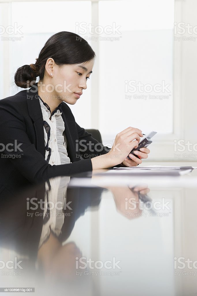 Businesswoman using mobile phone at conference table, side view royalty-free stock photo