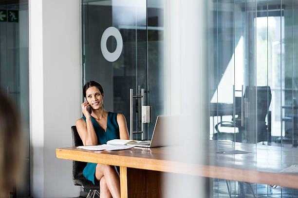 businesswoman using mobile phone at desk - business woman phone stockfoto's en -beelden