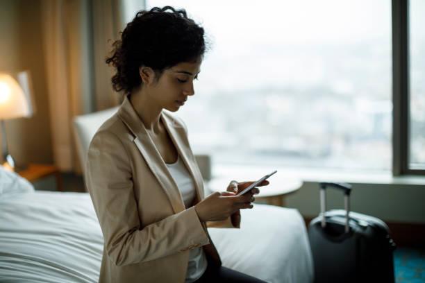 geschäftsfrau mit handy in einem hotelzimmer - hotels in der türkei stock-fotos und bilder