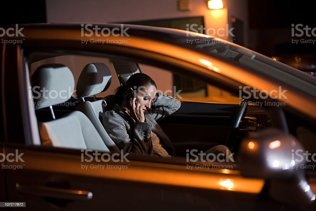 Businesswoman using mobile phone in car at night royalty-free stock photo