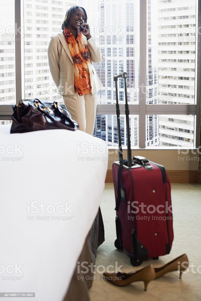 Businesswoman using mobile phone in hotel room, smiling royalty free stockfoto