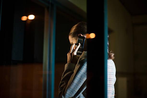 Geschäftsfrau mit Handy im Büro bei Nacht – Foto
