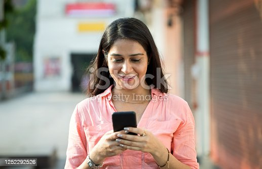 istock Businesswoman using mobile phone outdoors in city 1252292526
