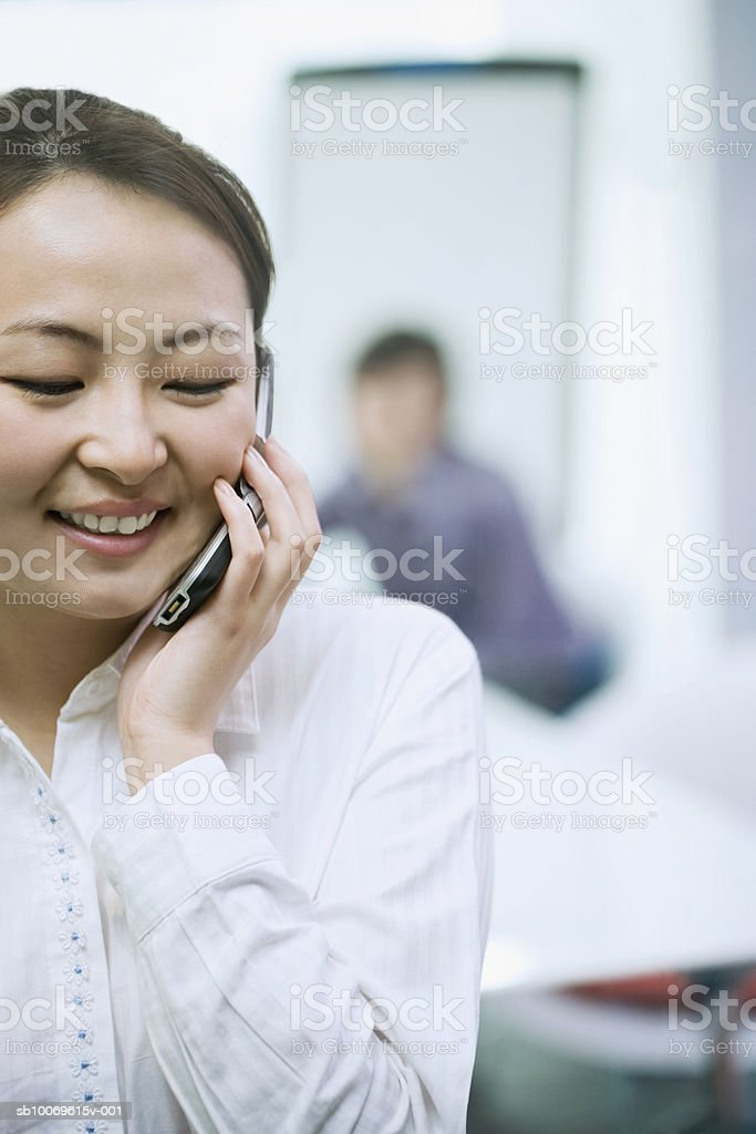 Businesswoman using mobile phone, smiling royalty free stockfoto