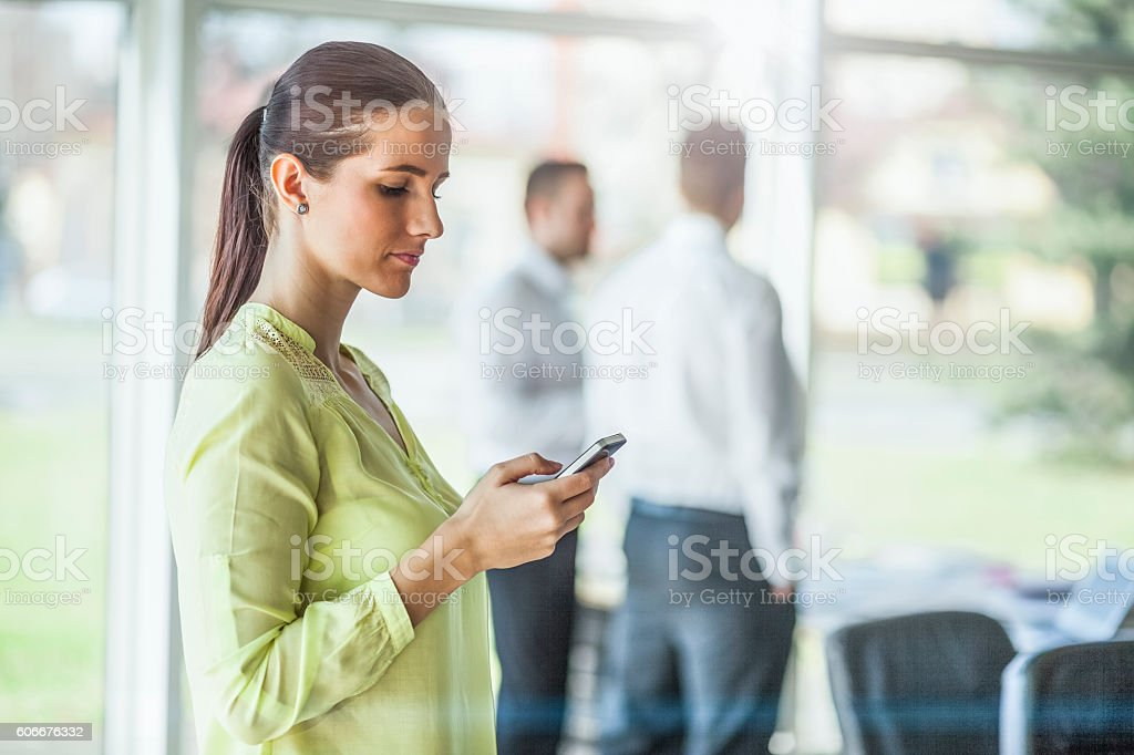 Businesswoman using mobile phone with male colleagues in background stock photo