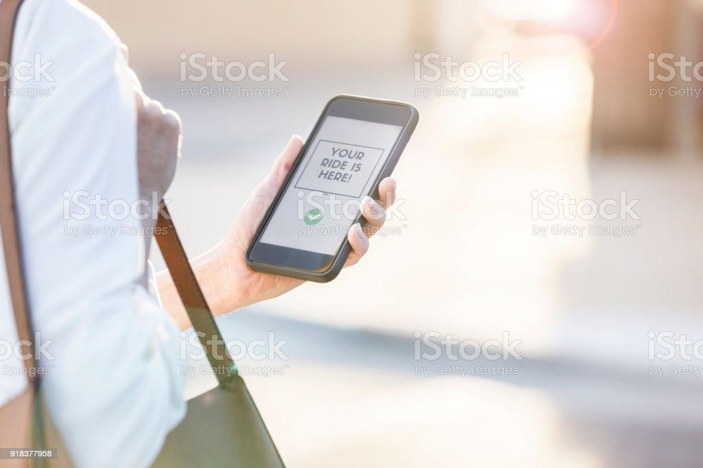 Businesswoman using mobile ride share app stock photo