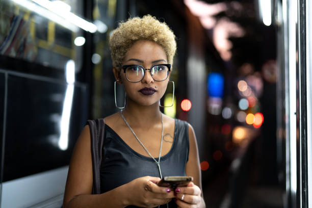 Businesswoman using mobile with city on background Always Connected afro caribbean ethnicity stock pictures, royalty-free photos & images