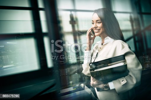 istock Businesswoman using phone and holding folders 665475290