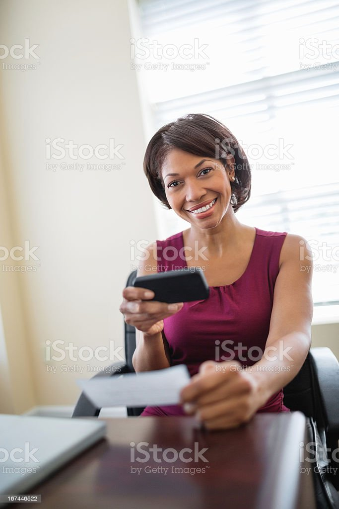 Businesswoman Using Phone To Deposit Check stock photo