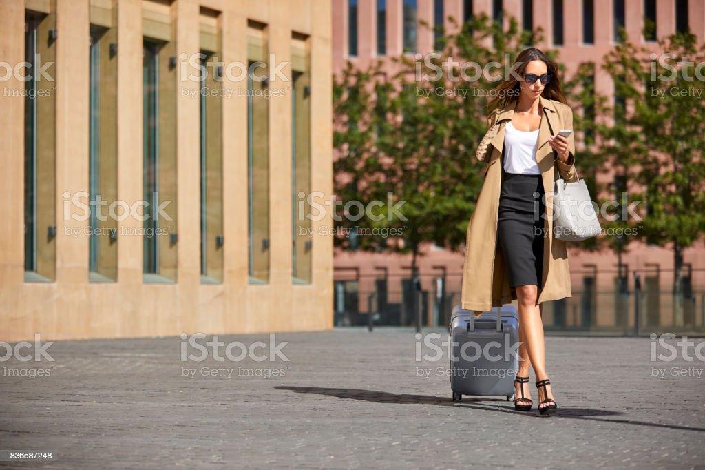 Businesswoman using phone while pulling luggage stock photo