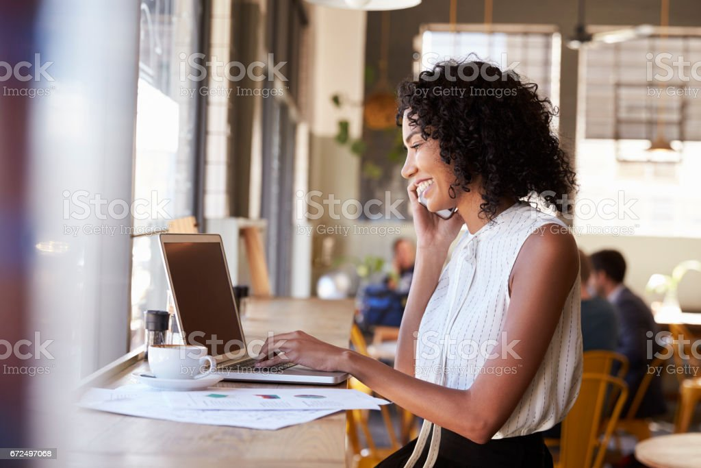 Businesswoman Using Phone Whilst Working In Coffee Shop stock photo
