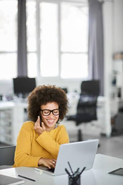 Geschäftsfrau mit Smartphone und Laptop im Büro. – Foto