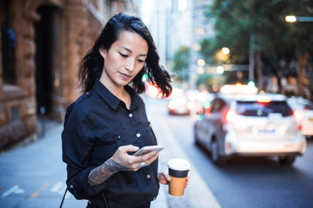 Businesswoman using smart phone and waiting for a taxi stock photo
