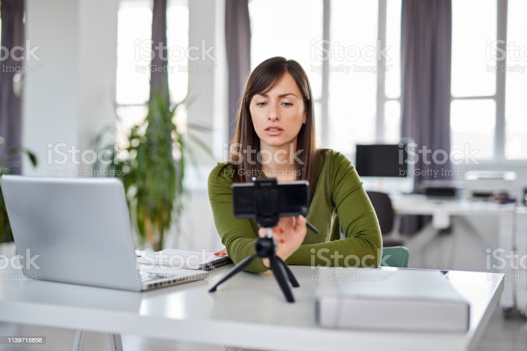 Businesswoman Using Smart Phone For Video Call In Office