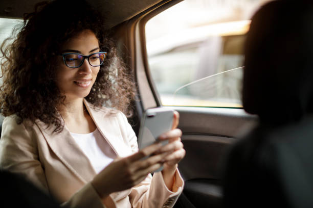 Businesswoman using smart phone in a car stock photo