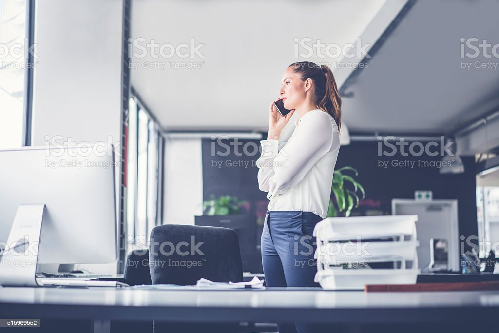 Businesswoman using smart phone in office stock photo
