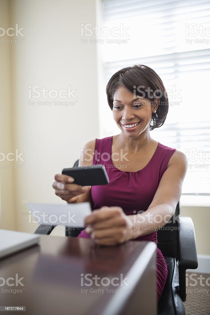 Businesswoman Using Smart Phone To Deposit Check stock photo
