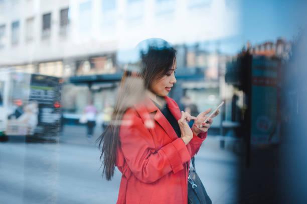 Geschäftsfrau mit Smartphone während des Wartens auf den bus – Foto