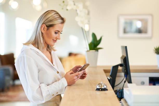 Geschäftsfrau mit Smartphone an der Hotelrezeption – Foto