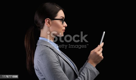 istock Businesswoman Using Smartphone Face Recognition System On Black Background 1176771898