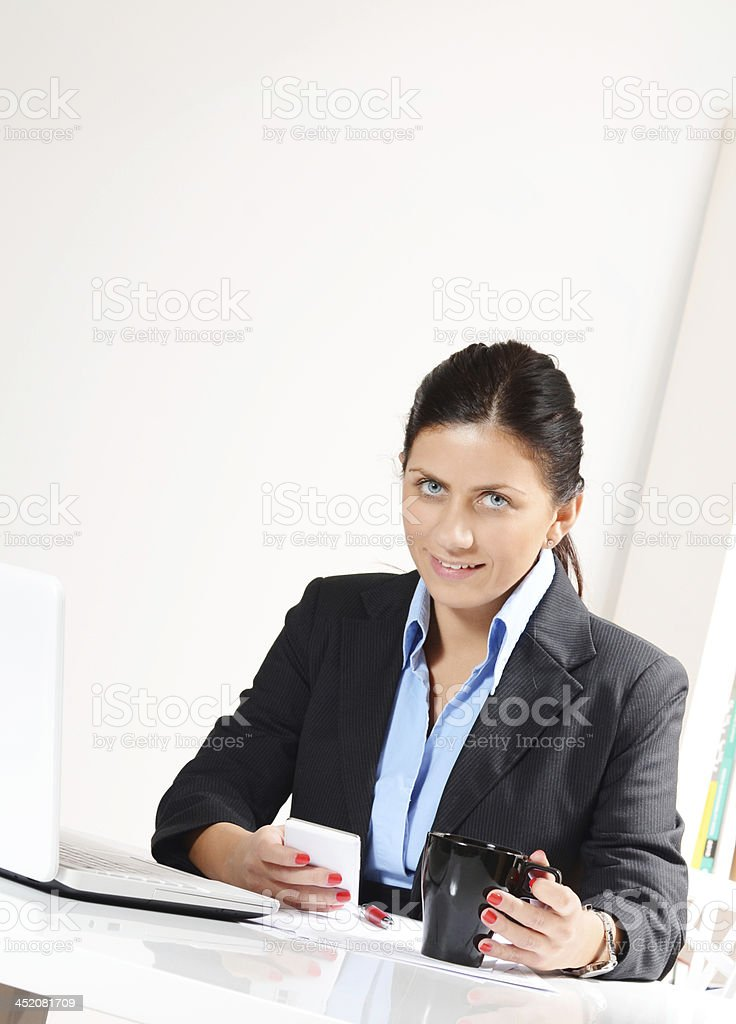 Businesswoman using smartphone in office and drinking coffee royalty-free stock photo