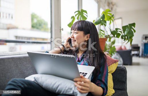 Young asian businesswoman using mobile phone while lying on sofa with a laptop. Female making a phone call during work break at new office.