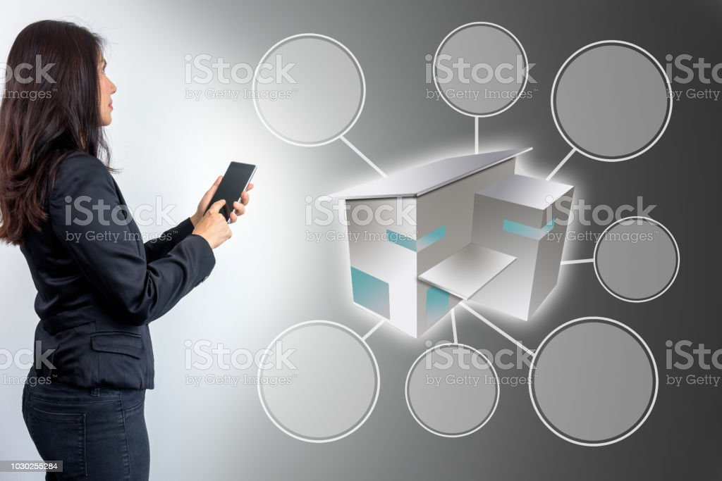 Businesswoman (Architect - Interior designer) using smartphone, working with 3D home & blank icon on futuristic virtual screen for advertising stock photo