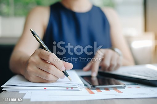 Businesswoman using smatphone for analysis maketing plan, Manager calculate financial report and graph chart.  Business, Finance and Accounting concepts