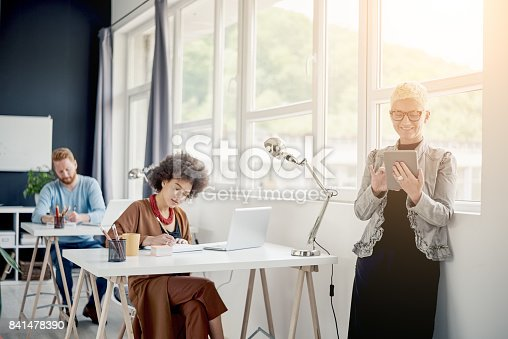 Businesswoman using tablet device in modern office. In background multi ethnic team